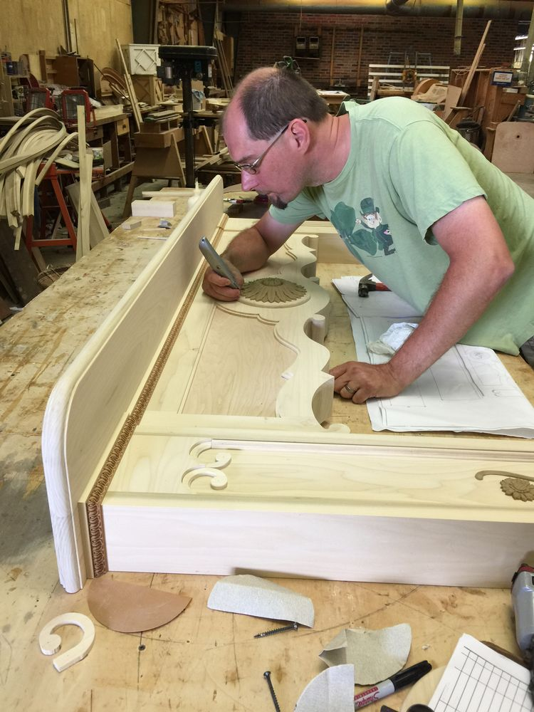 Driwood's skilled craftsman works on a French style mantel